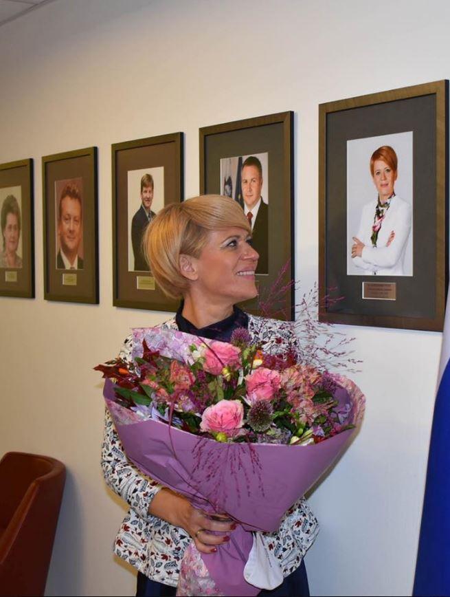 Slovo: Aleksandra Pivec občuduje svojo sliko na steni kmetijskega ministrstva. Vir: Facebook