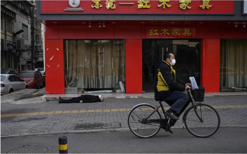 Grozljiv prizor iz Wuhana: mrtev človek leži na cesti, kolesar pelje naprej